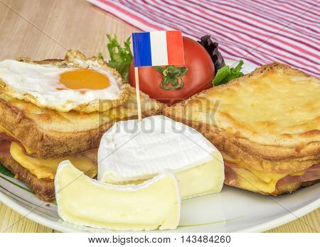 Plate with traditional french food - Close up over a plate with french white cheese salad tomato and the traditional croque sandwiches made with melted cheese ham and fried egg.