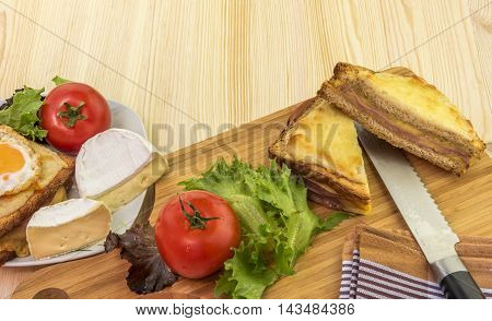 Sliced sandwich and fresh vegetables - Delicious food on a wooden table french sandwiches called croque madame and croque monsieur tomatoes white cheese and salad.