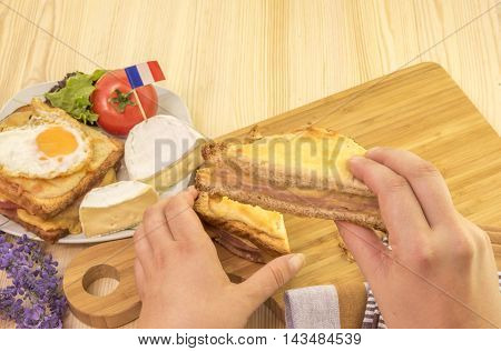 Woman's hand holding a sandwich slice - Food photography with a slice from a delicious french sandwich called croque monsieur and in the background a plate with other french products.