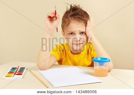 Little preoccupied artist in a yellow shirt is thinking what to paint