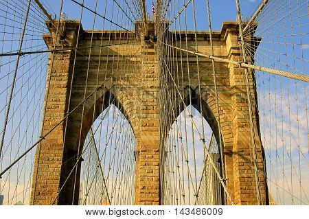 New York City - November 5 2005: The iconic west tower gothic arches of the 1875 Brooklyn Bridge over the East River