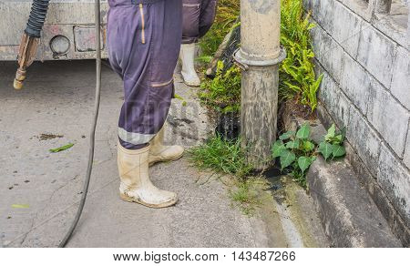 image of city officer inspecting the sewers of the streets .