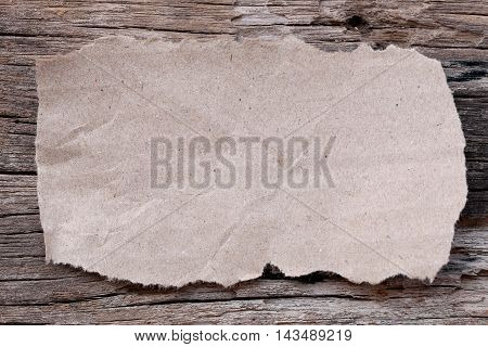 Brown tear cardboard on old wooden floor concepts about education or note text.