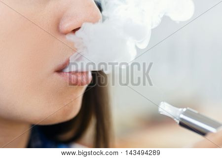 closeup of woman smoking electronic cigarette and enjoying smoke. Copy space. Closeup detail of female with electronic cigarette horizontal shot. Girl smokes and exhaling flavored steam. Concept: safe way of smoking how to stop smoking