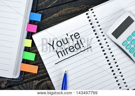 You're Hired text on notepad and hand calculator