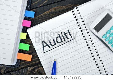 Audit text on notepad and hand calculator