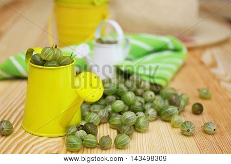 Small watering can with fresh gooseberries on wooden table
