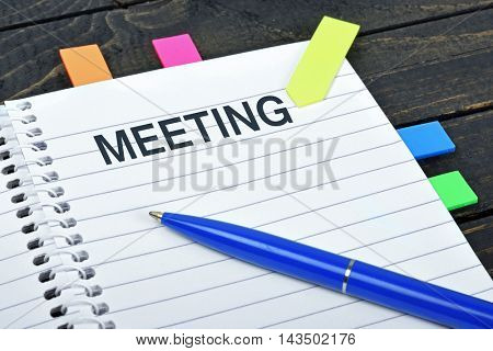 Meeting word on notepad and pen