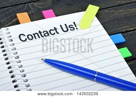 Contact us word on notepad and pen