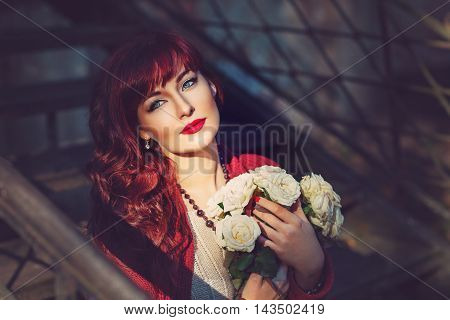 Beautiful young woman in wool red scarf sitting on old house stairs holding flowers. Early fall. Outside shot. Ambient light. Closeup portrait. Copy space.