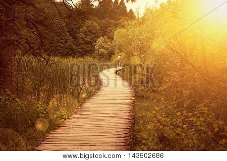 Wooden tourist path in Plitvice lakes national park in the sunset