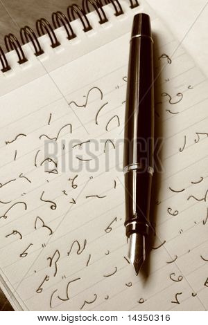 Classic fountain pen resting on pad with shorthand.  Sepia tone.  The shorthand is Dacomb.