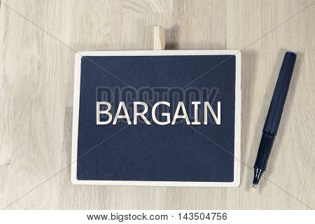 BARGAIN written on a chalkboard with pen.wooden desk.