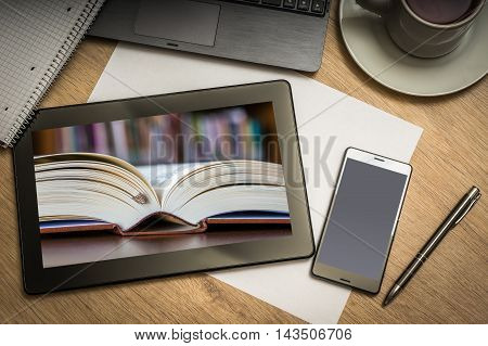 Digital tablet on business table with open book in library on screen and mobile phone paper pen laptop and cup of coffee - above view