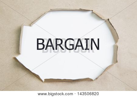 BARGAIN word written under Brown torn paper.
