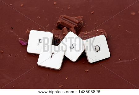 picture of a The word PTSD written on chocolate background.