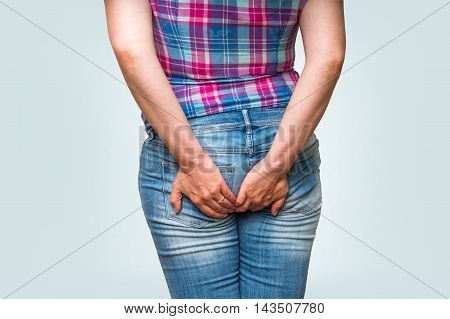 Woman Holding Her Butt Isolated On Blue Background