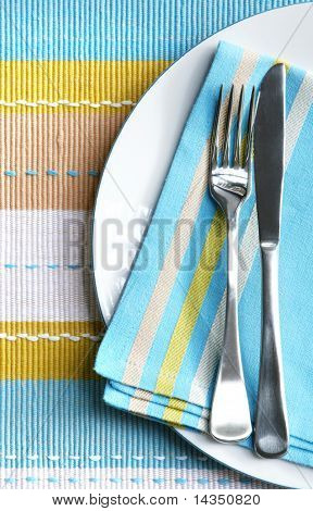 Place setting with silver fork and knife on pastel napkin, and matching placemat.  Vertical view.