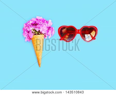 Ice Cream Cone With Flowers And Red Sunglasses Heart Shape Over Blue Background Top View