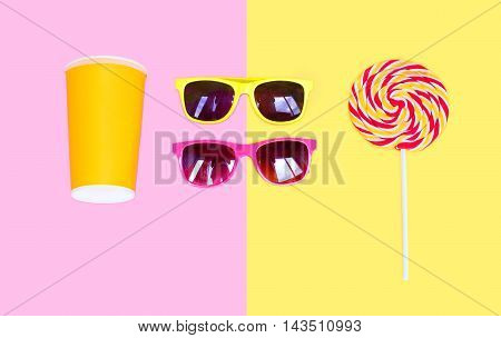 Two Sunglasses And Colorful Lollipop Caramel On Stick With Cup Juice Over Pink Yellow Background Top