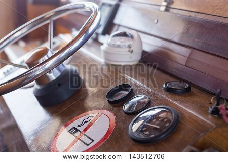 Old cabin ship with a metal steering wheel and instrument panel, blurry