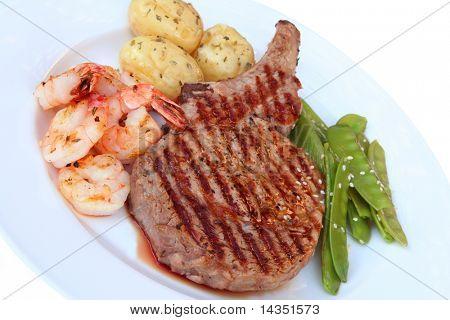 Rib-eye steak with shrimps and vegetables.