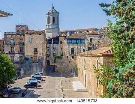 Girona Spain - July 30 2016. Les Aligues building University of Gerona in Placa de Sant Domenec square with bell tower of Santa Maria cathedral in background. Gerona Costa Brava Catalonia Spain.