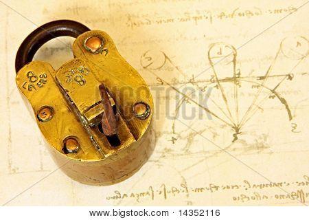 Antique brass padlock, on a page of Da Vinci's writings.  19th Century vintage Indian padlock.