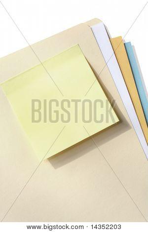 Blank yellow sticky note on a manila folder.