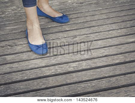 Female legs in shoes on a wooden floor. Toned photo.