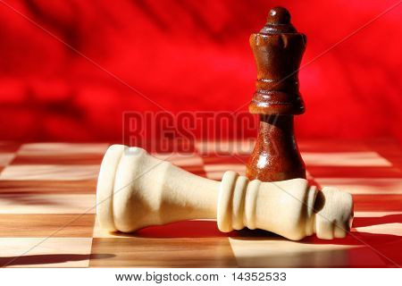 Chess pieces in checkmate.  Wooden king and queen, with vibrant red background. Natural light.