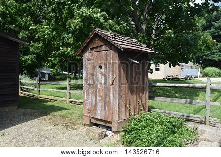 a old wooden outhouse with a wooden roof.
