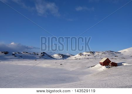 Wooden house on the snowcovered Norwegian mountain plateau Hardangervidda