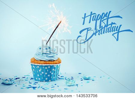 Birthday cupcake with sparkler on blue background