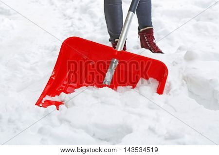 Winter concept. Woman removing snow with red shovel