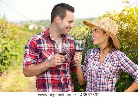 Romantic couple looking each other and toasting with wine in  vineyard