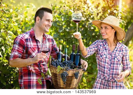 young couple winegrower tasting wine in vineyard