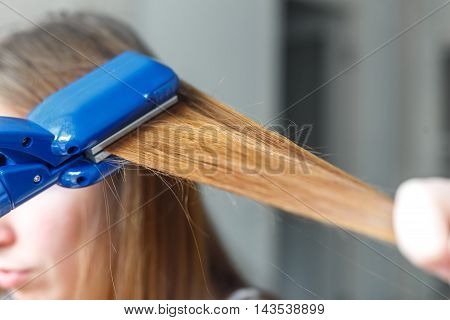 Straightener. Hairdresser hairstyle beautiful model using straightener. Closeup. Selective focus