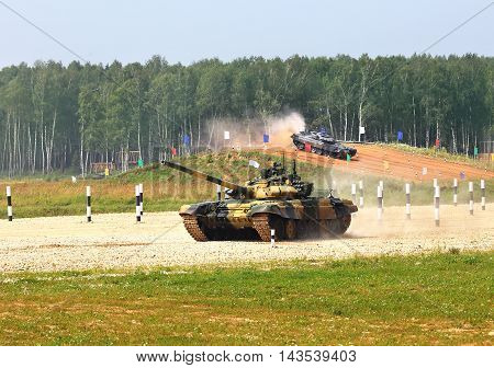 Two main battle tanks on a march over rough terrain