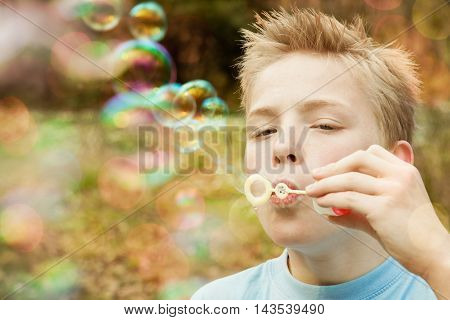 Male Child Blowing Bubble Outdoors