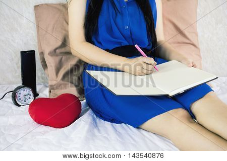 Women Writing Down On Blank Workbook Or Booklet While Sitting On Bed