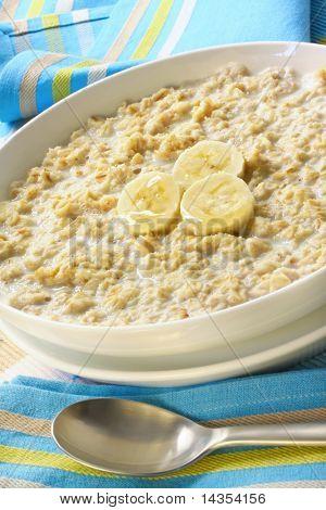 Bowl of porridge, with banana and honey.  A sunny, healthy oatmeal breakfast.