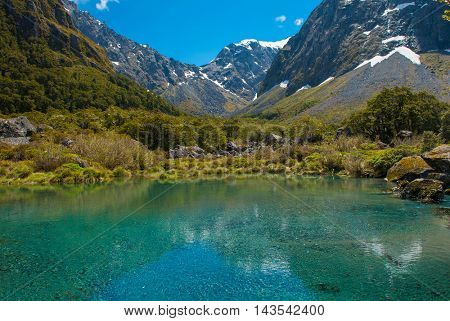 Gertrude Seddle with a snowy mountains and a turquoise lake, Fiordland national park, New Zealand South island