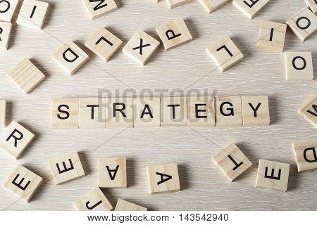 Strategy word written on wood block. Wooden abc.