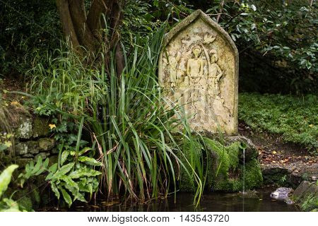 Holy well and spring at St. Mary's Church, Charlcombe. Quiet garden in churchyard near Bath Somerset UK with stone by well fed by spring water famed for its healing properties