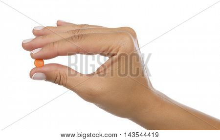 Pink pill in between the fingers of a woman isolated on white background.