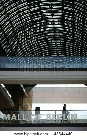 BERLIN, GERMANY - JUNE 21: Guests and visitors go over a bridge with Glass railings under the roof of the Mall of Berlin on June 21, 2016 in Berlin.