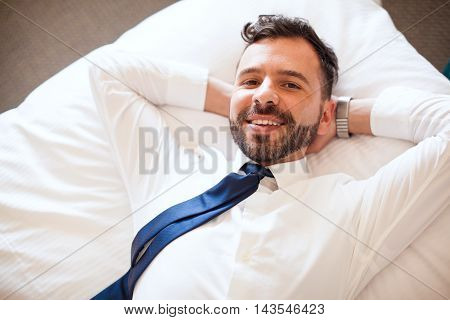 Hispanic Businessman Relaxing On A Bed