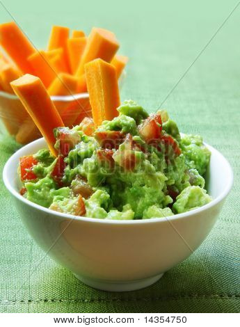 Healthy avocado guacamole served with carrot sticks.