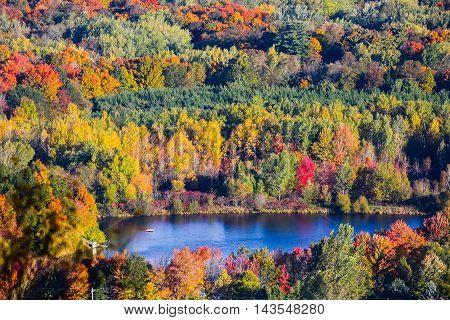 Blue lake surronded by fall foilage in Wisconsin.